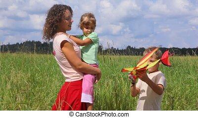 boy showing airplane to his mother and sister