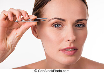 Pretty young woman using tweezers