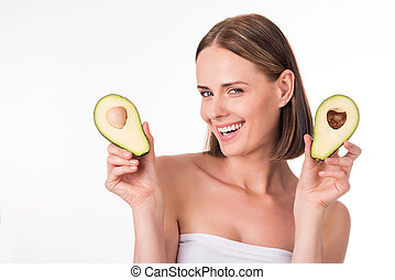 Pretty young woman holding avocado - Healthy food Positive...