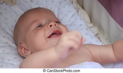 smiling baby laying in the crib and raising his hands