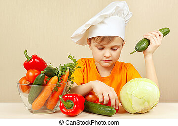 Little boy in chefs hat with vegetables at table