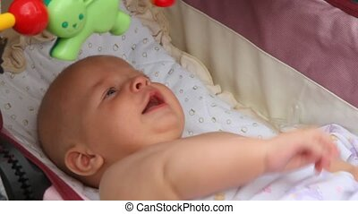 crying baby, waving his hands, looking at the toys