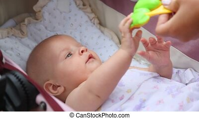 baby trying to sit up while holding mothers hands