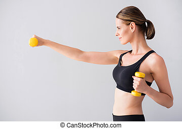Confident young woman with dumb bells
