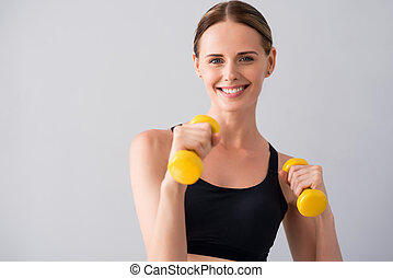 Cute young woman with dumb bells