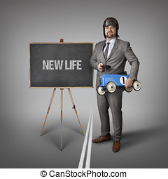 New life text on blackboard with businessman and toy car