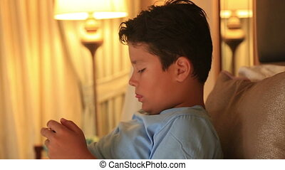 Portrait of a funny young boy playing on smartphone at home
