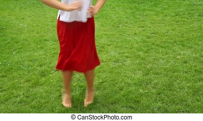 woman dances barefoot on the grass