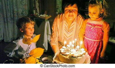 family blowing out candles on cake