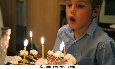 boy blowing out candles on cake