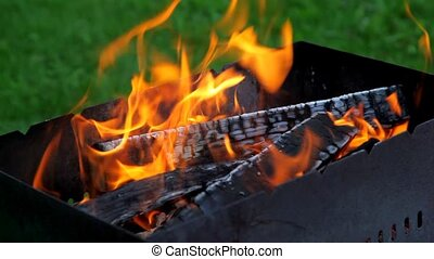 flame over logs in the grill, close-up