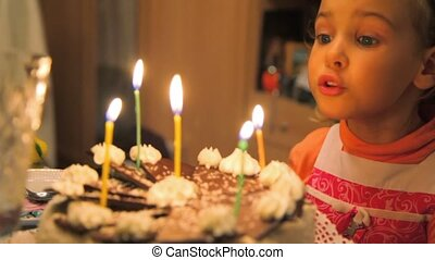 little girl blowing out candles on cake