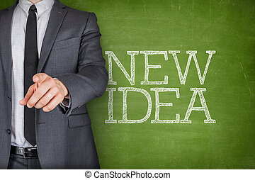New idea on blackboard with businessman - Concept on...