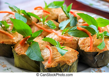 Thai steamed curry fish in banana leaf cups decorated with...