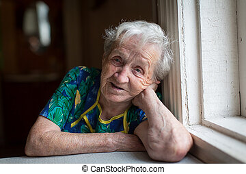 Elderly woman portrait sitting at the table.