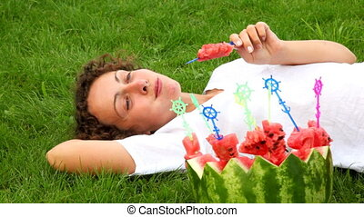 yang woman eating watermelon while laying on grass