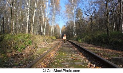 boy running along railroad tracks, to camera