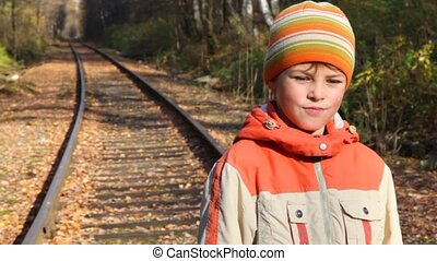 portrait of boy standing on railroad tracks