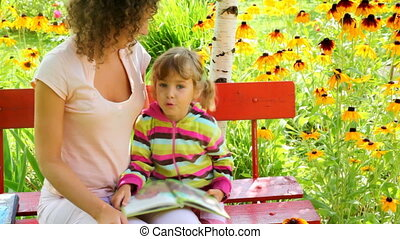 mother and daughter reading book on the bench in the yard