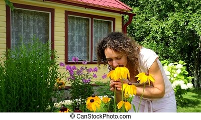 yang woman smelling yellow Echinacea flowers