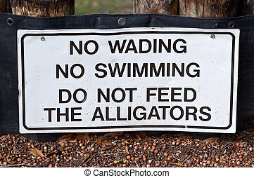 Don't Feed Alligators - White warning sign with black...