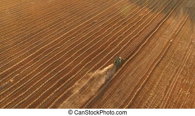 Aerial view of moving harvester Trail of dust behind machine...