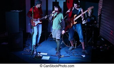 musical group of four persons live on stage in night club