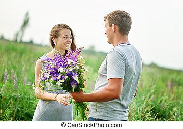 young couple in love walking on the summer meadow