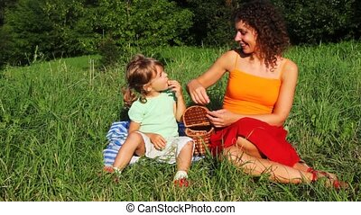 mother and daughter sits on lawn near forest and eats sweet cherry from basket