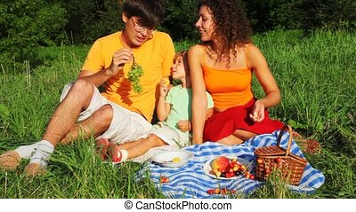 father, mother and daughter rests together on grass near trees and eats vine