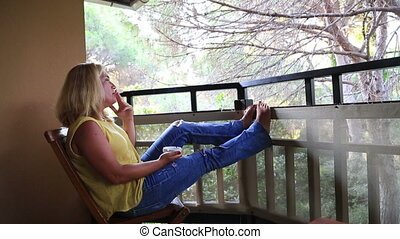 Woman smoking cigarette - Woman sitting on the balcony and...
