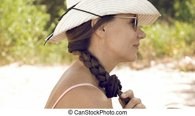 Woman is stroking her long hair and plait outdoors on sunny...