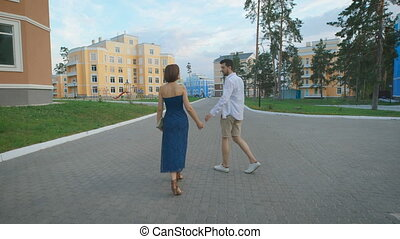 Man and woman strolling along the fashionable residential...