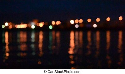 Night traffic with unfocused city lights reflected in water....