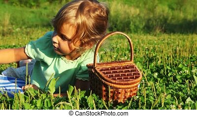 little girl lies in grass, takes cherry from basket and eats it