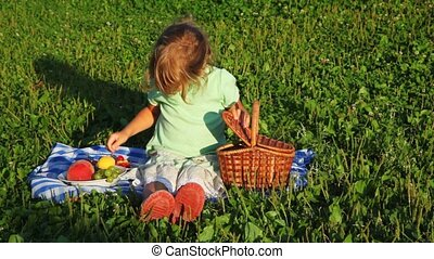 little girl sits on lawn and shifts cherries from basket in plate with fruit
