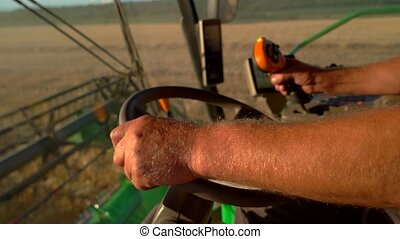 Hand on combines steering wheel Harvester is moving on field...
