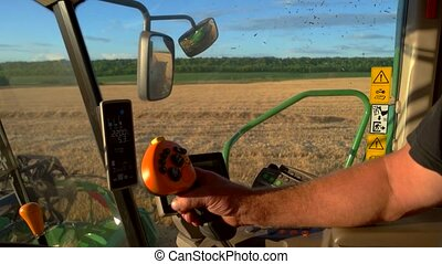 Man's hand on harvester controls. Machine is moving through...