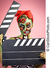 clapperboard - Pin-up zombie woman holding clapperboard over...