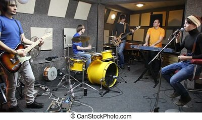musical group of five persons playing in studio