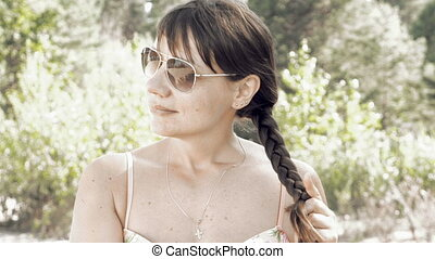 Woman plaits her long hair and stroking it outdoors on sunny...