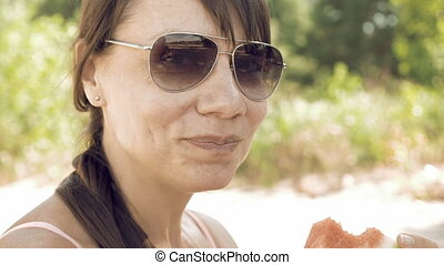 Smiley woman eats an watermelon outdoors on summer sunny...