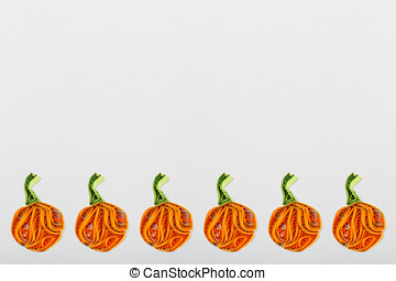 Pumpkins in quilling techniques for Halloween on a light...