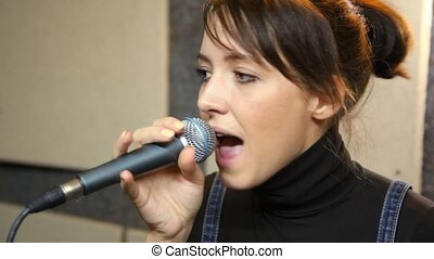 young female vocalist with microphone singing in studio