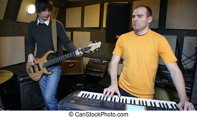 guitarist and keyboard player playing in studio