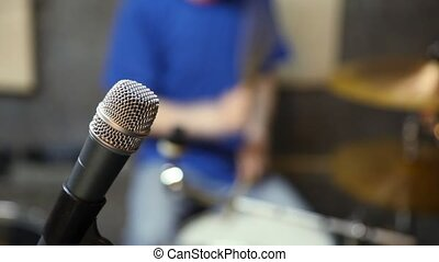 microphone and unidentified drummer in background in studio