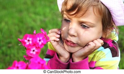 little girl close up near pink flowers look and talk