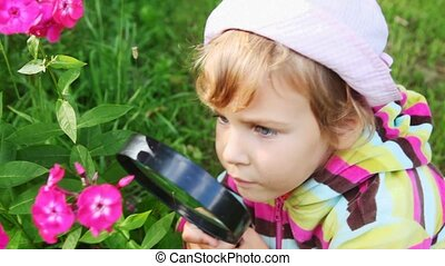 girl look on pink flowers through magnifying glass and talk in park
