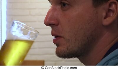 Stock video footage restaurant man drinks beer. Man takes a...