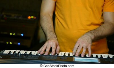 unidentified keyboard player playing on synthesizer in studio